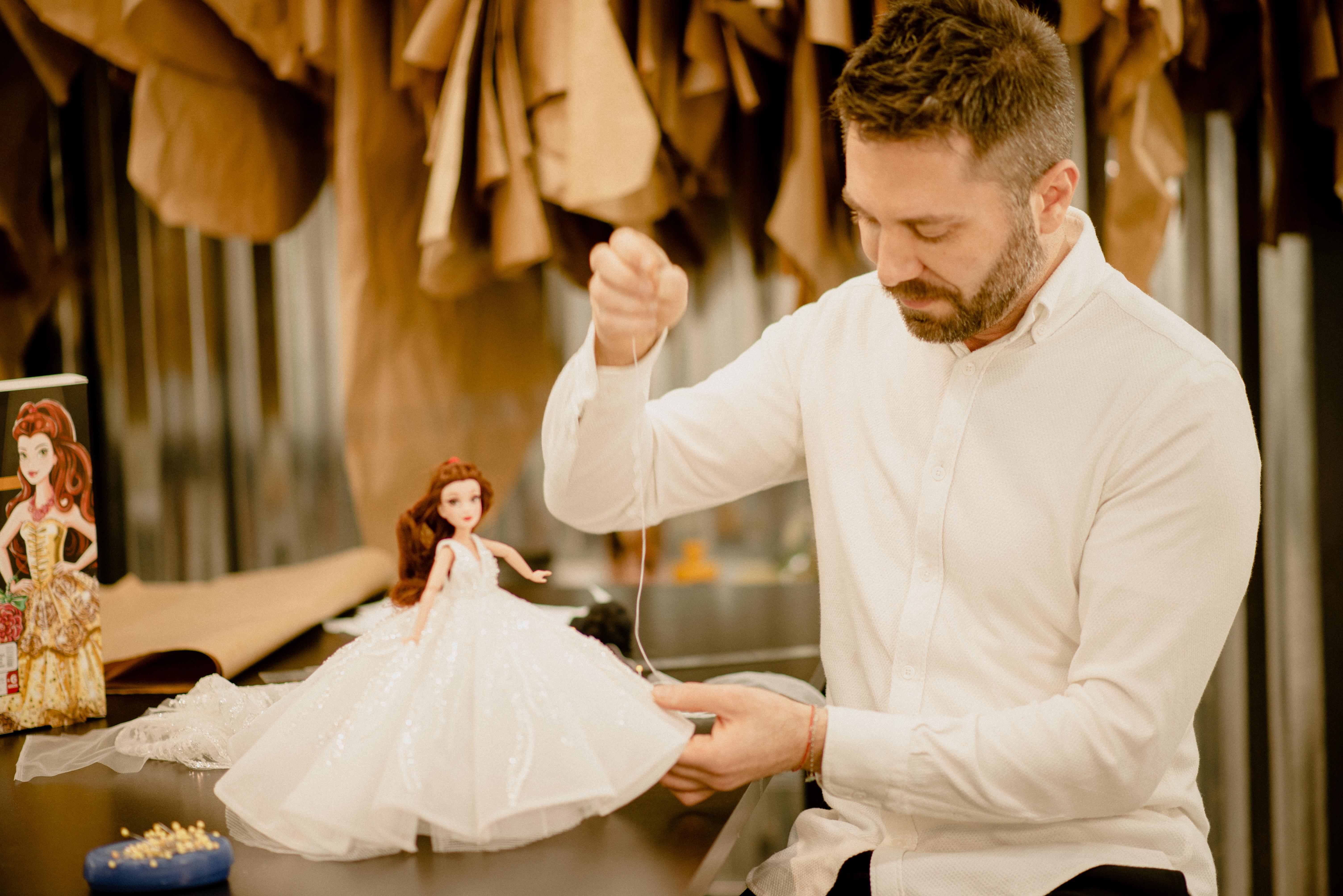 Lucas Anderi aparece costurando vestido de noiva em boneca. Veste camisa branca e calça preta.