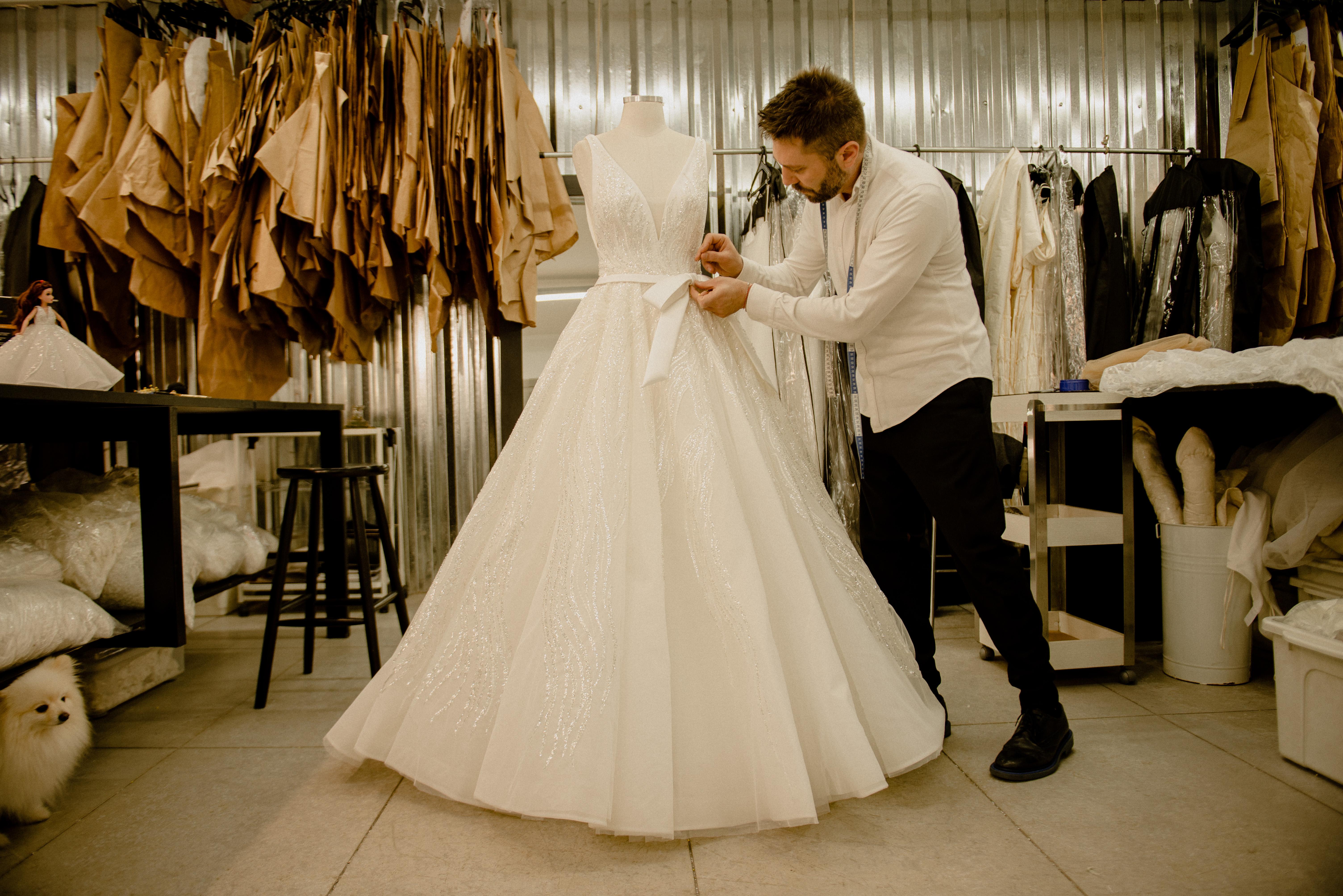 Lucas Anderi costura trecho de vestido de noiva na imagem. Aparece de paletó preto e camisa branca ao lado do vestido em seu ateliê.