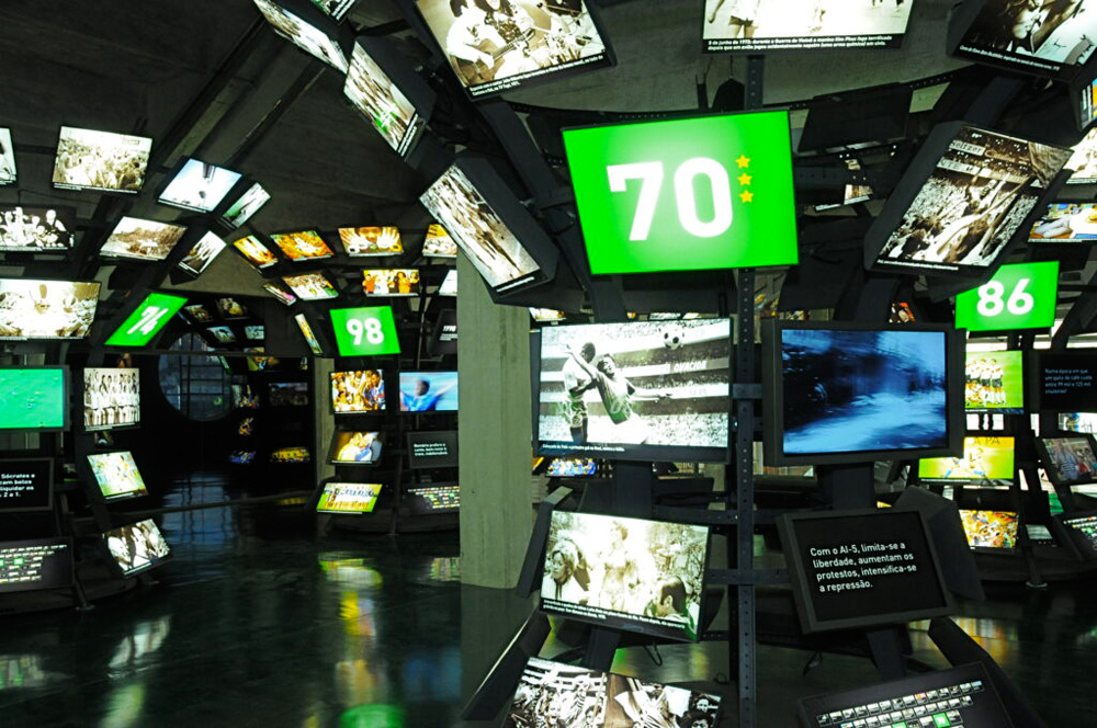 Dezenas telas alinhadas em colunas em uma sala expositivas mostram cenas de futebol