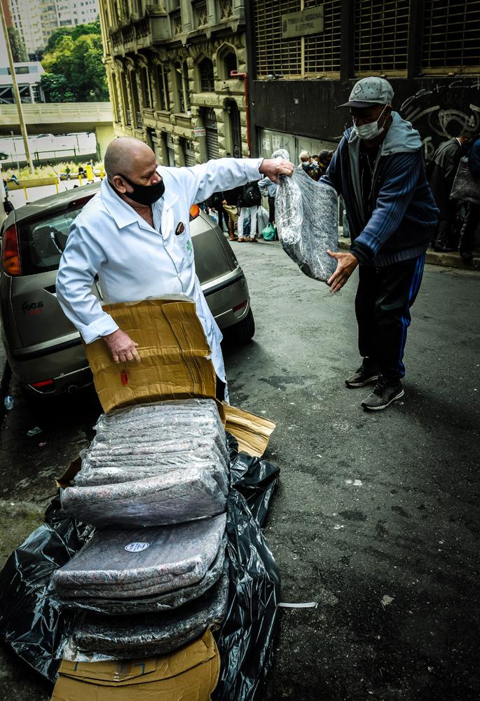 A imagem mostra Robson, com um carrinho cheio de cobertores, entregando um deles à outra pessoa na rua