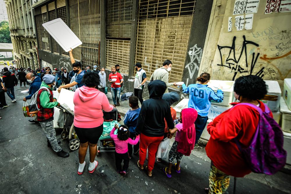 A imagem mostra uma fila de pessoas na rua em frente de grandes isopores onde há pessoas retirando marmitas de dentro.
