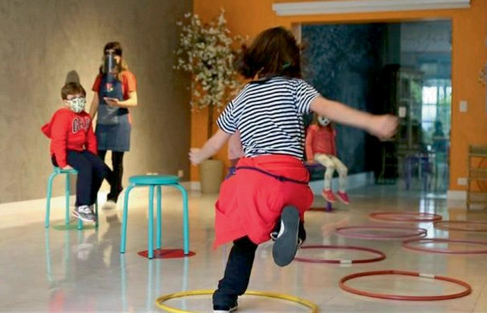 Criança pula entre bambolês enfileirados no chão