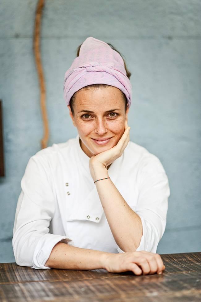 Chef Helena Rizzo sentada atrás de mesa vestida com dólmã e lenço lilás no cabelo, com o cotovelo apoiado sobre a mesa e a mão segurando a bochecha.