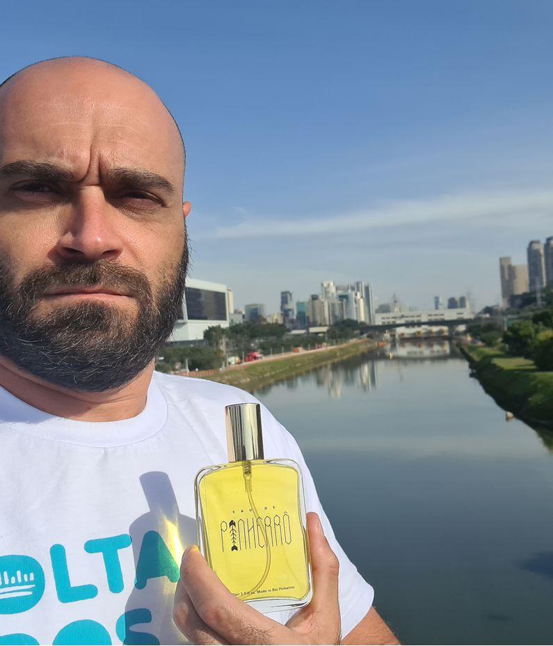 Marcelo Reis, porta-voz do movimento Volta Pinheiros, segura frasco de líquido amarelo em frente ao Rio Pinheiros. Ele é careca e tem barba.
