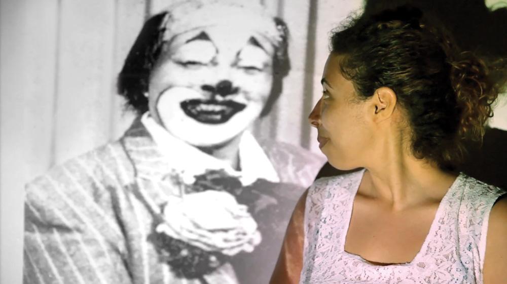 mariana de perfil olhando para tras, onde está sendo projetado o documentário de sua avó, com uma cena em que sua avó aparece vestida de palhaço