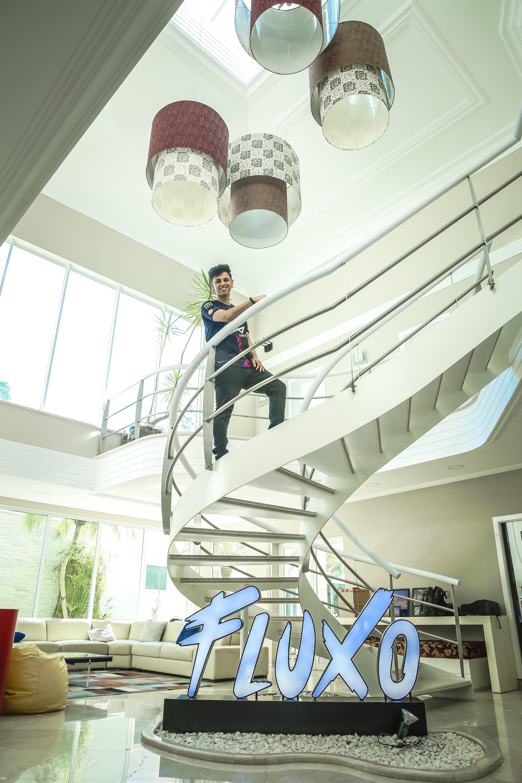 A imagem mostra Nobru em sua casa, na escada, sorrindo