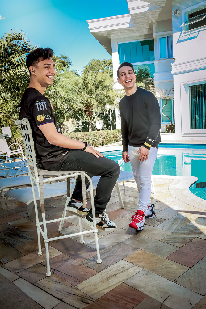 A imagem mostra Bruno, sentando em um banco na frente de sua piscina, junto de seu pai que está em pé. Ambos estão rindo.