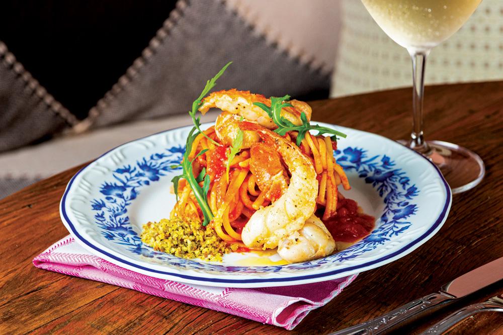 Sobre um prato branco decorado com detalhes em azul está o linguine coberto por lagosta ao lado de taça de vinho branco.