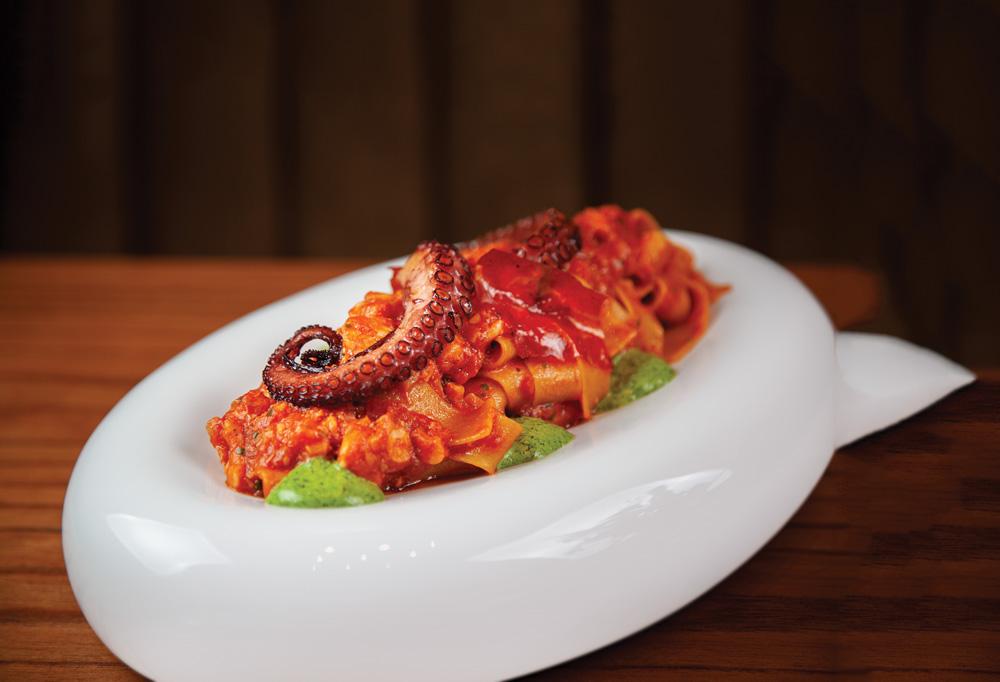 Prato oval de louça branca sobre mesa de madeira com macarrão ao molho de tomate coberto por tentáculo de polvo.
