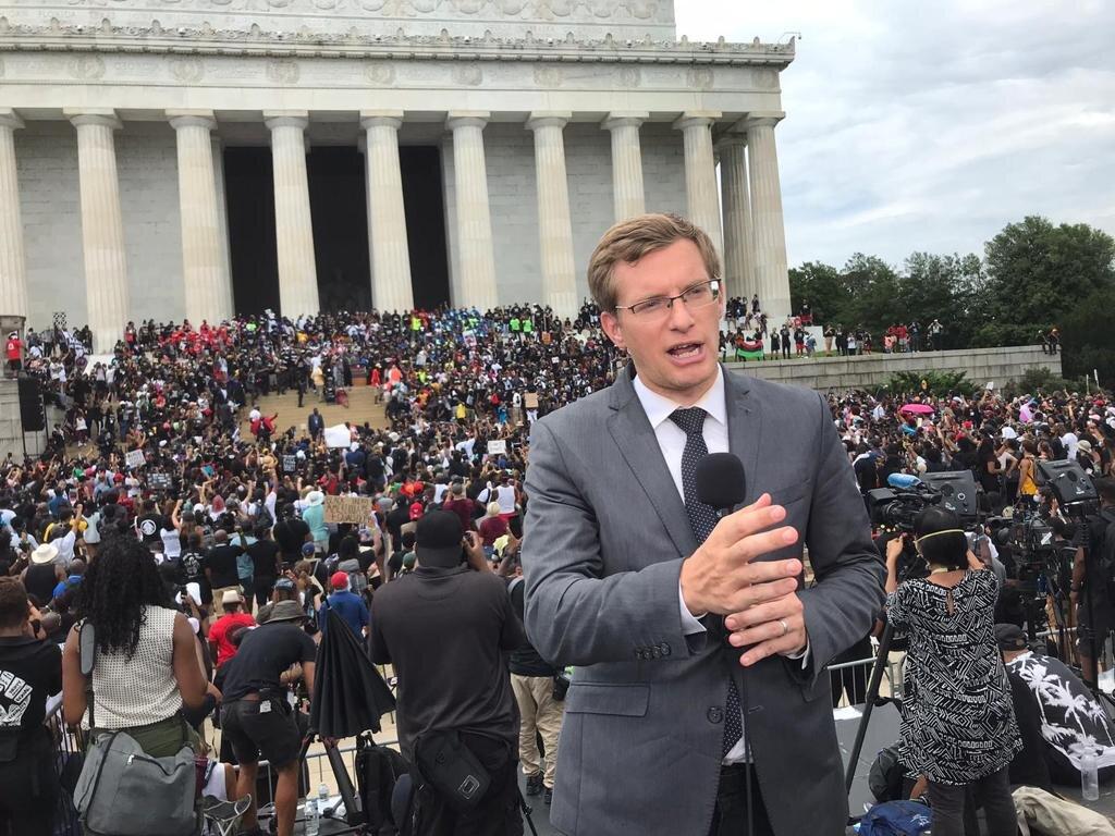 Philip Crowther aparece de terno falando em microfone. Ao fundo, multidão ocupa entrada do Capitólio dos Estados Unidos.