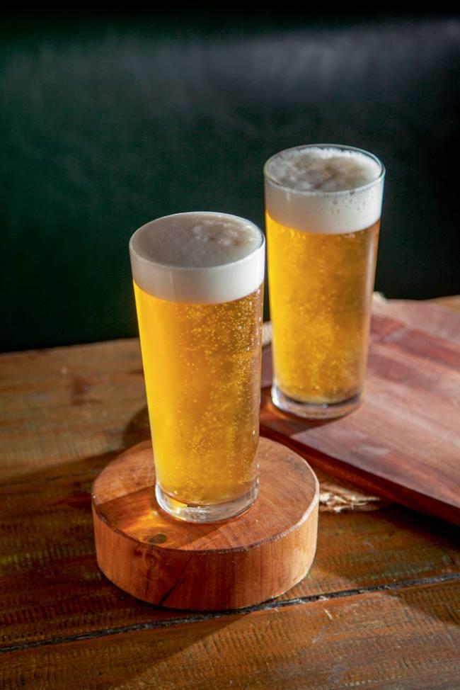 Dois chopes amarelados e com colarinho em copos altos sobre superfície de madeira.