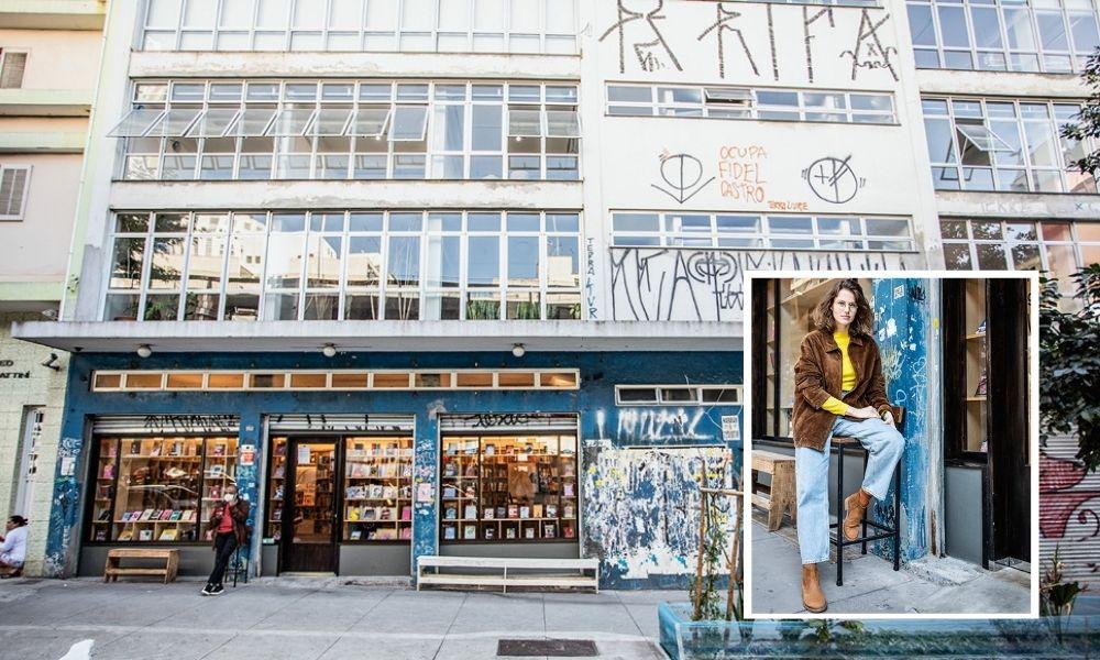 A imagem mostra a fachada do prédio e a livraria instalada no inferior com janelas grandes de vidro, sendo possível ver internamente. Há uma pequena foto na montagem de Stein, sentada em um banquinho em frente a livraria.