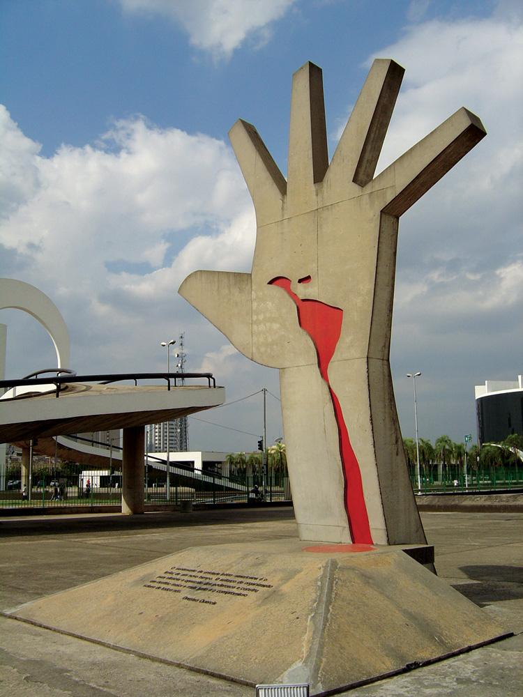 A imagem mostra a escultura na Praça do Sol, uma mão aberta elevada com um desenho vermelho na palma dela.