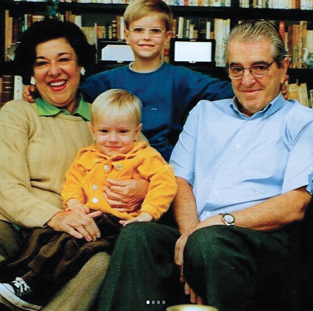 ruth rocha com seu marido, eduardo rocha, e seus netos pedro e miguel, sorrindo posando para a foto. pedro está sentado no colo de ruth, que está sentada ao lado de eduardo. miguel está de pé atrás deles com um braço nas costas de cada avô