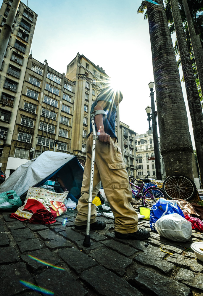 A imagem mostra uma foto, vinda do chão, observando Paulo, muleta, andando. No fundo, há uma barraca na calçada e itens espalhados pelo chão.