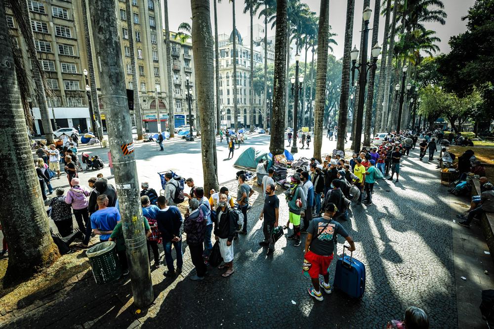 A imagem mostra uma longa fila formada na praça da Sé.