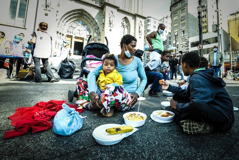 A imagem mostra Kelly, com uma criança de colo e olhando para outras duas no seu lado, sentados todos na calçada. No meio da roda, há marmitas, tudo no chão.