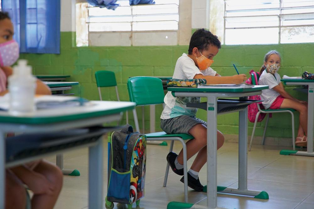 A imagem mostra alunos em uma sala de aula, distanciados, usando máscara enquanto escrevem em cadernos nas suas mesas.