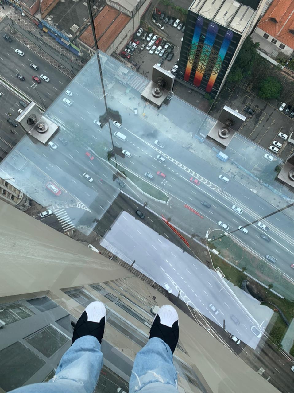 Foto mostra dois pés no chão de vidro de um mirante. Lá embaixo, aparece a cidade na região do Centro.