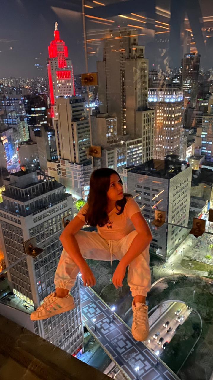 Uma menina aparece sentada no box de vidro do Sampa Sky com a vista noturna do Centro ao fundo. O Farol Santander aparece em destaque.