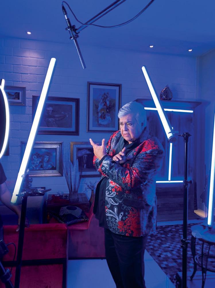 Sidney Magal está de pé em sala iluminada com dois bastões azuis. Ele veste blazer azul e vermelho e ergue a mão esquerda em frente a uma câmera.