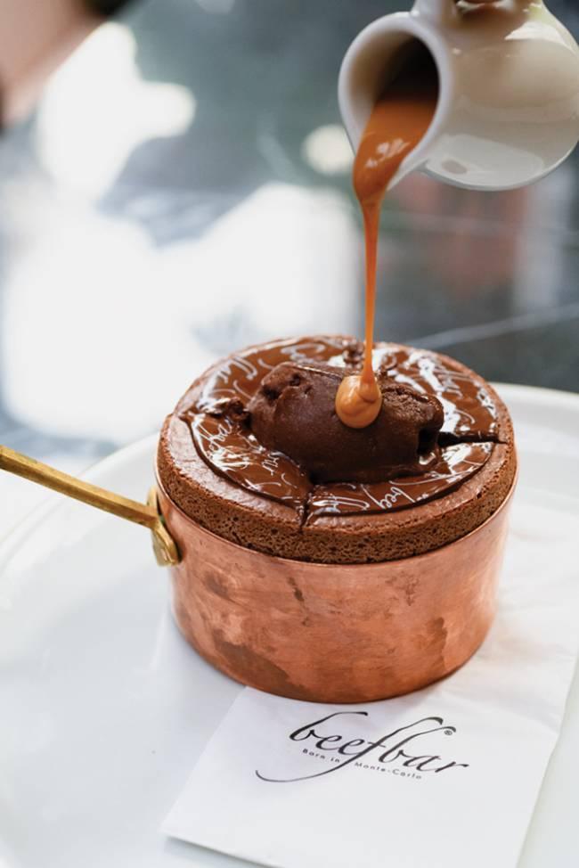 Suflê de chocolate em panelinha de cobre sobre prato de louça branca do Beefbar recebendo calda de caramelo de jarrinha de louça branca.