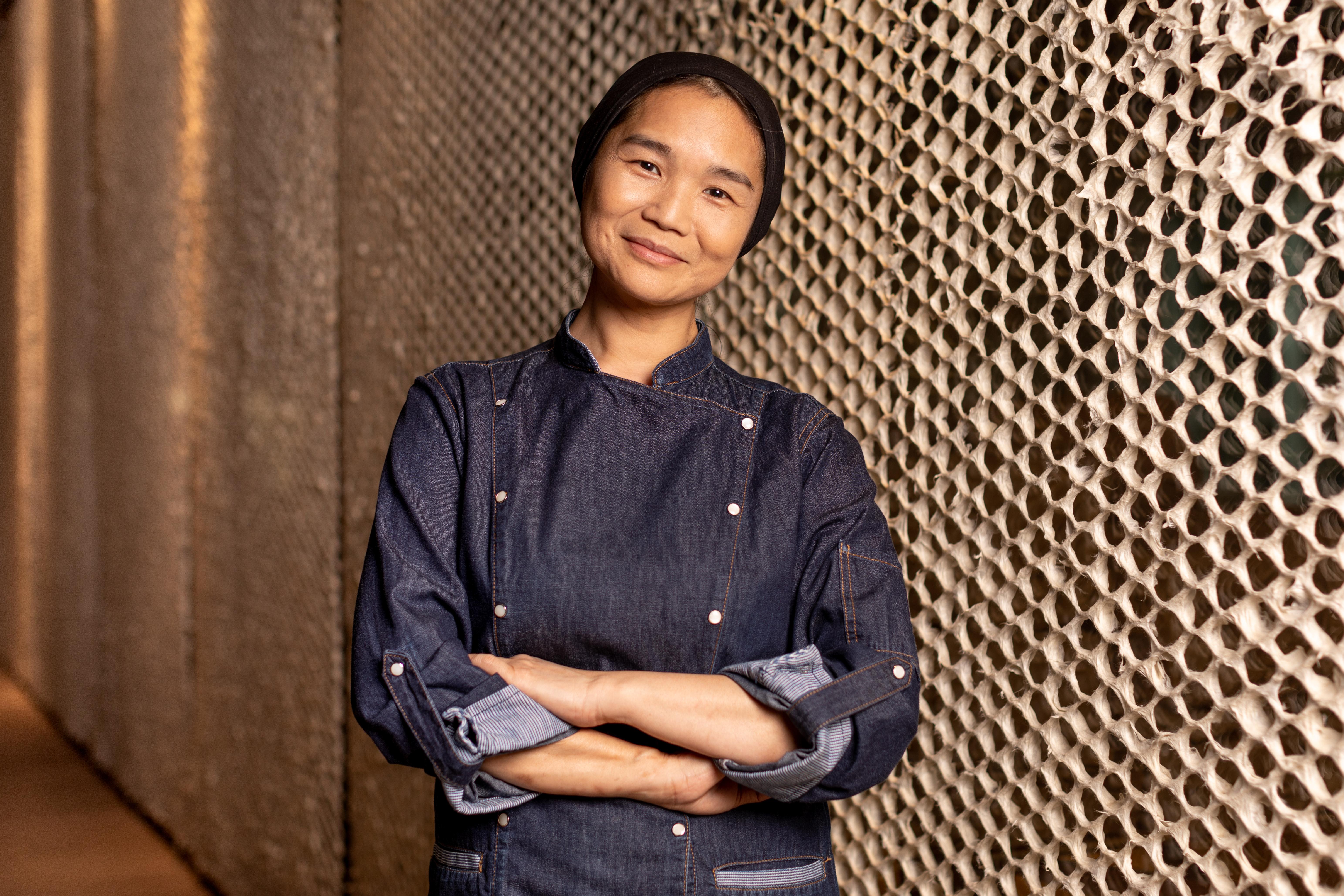 A chef Telma Shiraishi sorrindo de braços cruzados em frente à parede de textura rendada.
