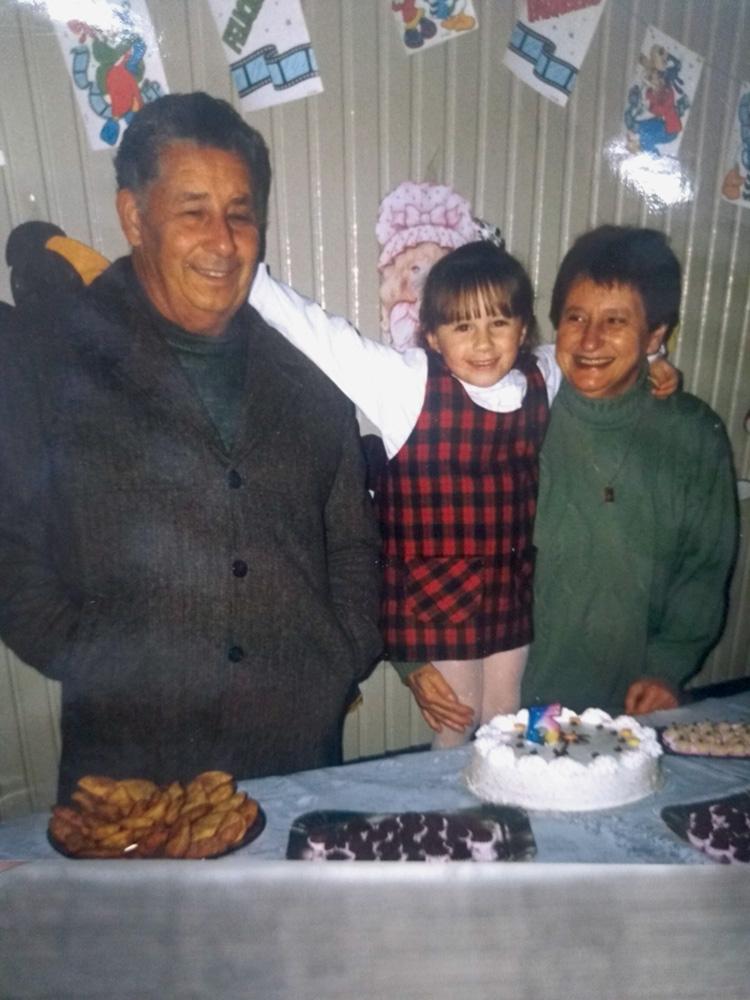 thais abraçada com os avôs José e Zilda, em sua festa de aniversário de 5 anos. à frente deles, uma mesa com bolo e docinhos