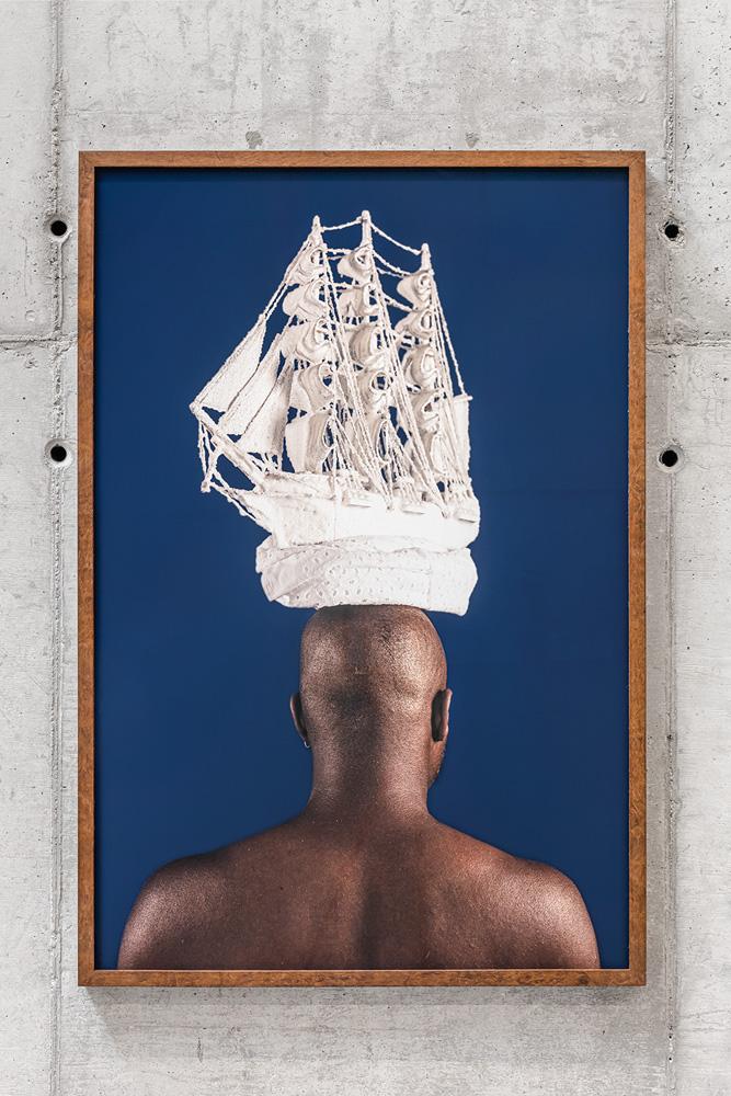 pessoa negra de costas com embarcação marítima branca apoiada em sua cabeça