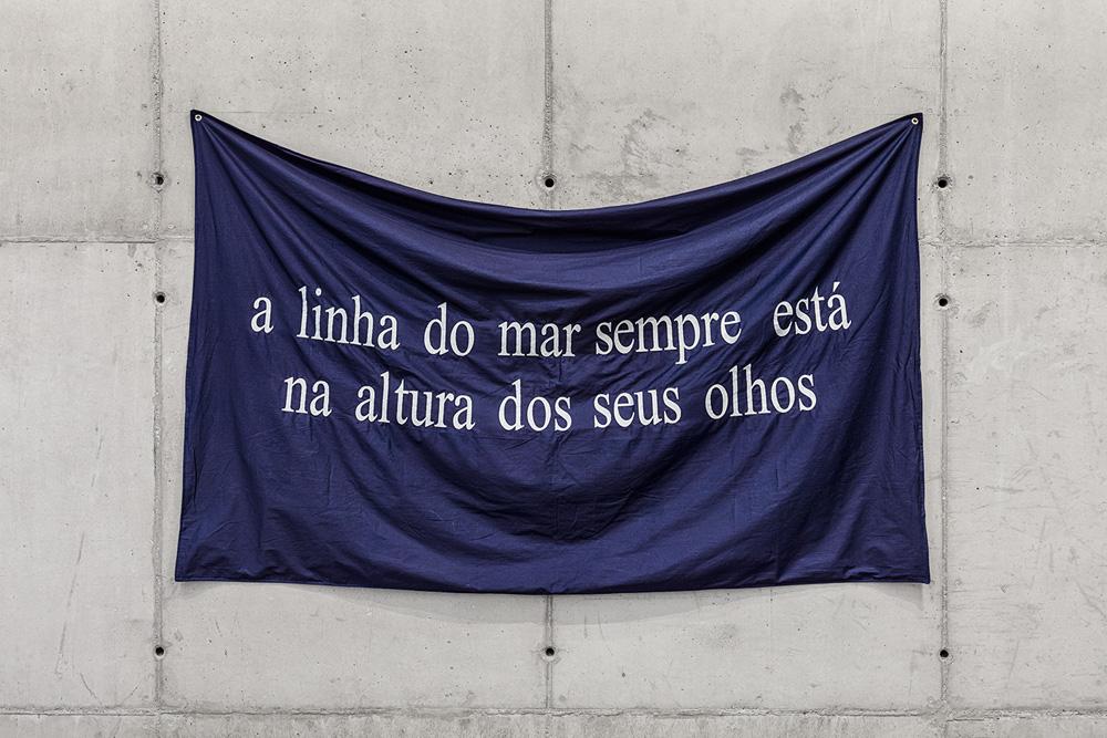 faixa azul com a seguinte frase, em branco: a linha do mar sempre está na altura dos seus olhos