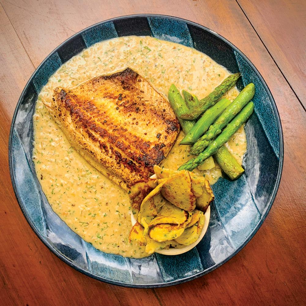 Sobre uma mesa de madeira, um prato azul dispõe truta grelhada e seu molho, junto aos aspargos e pequenas panquecas rasgadas.