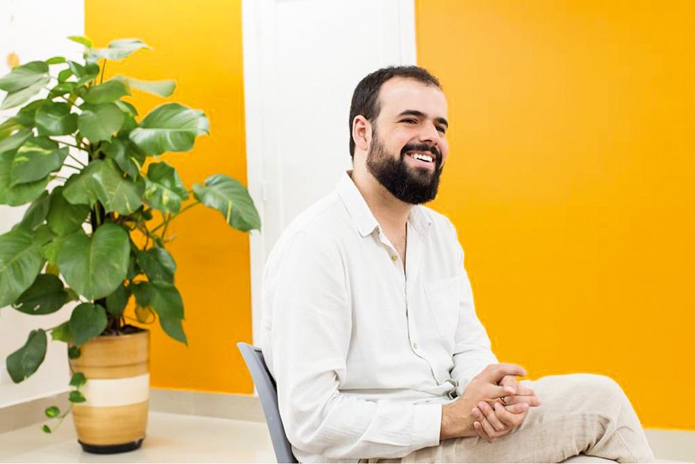 nickson gabriel sentado sorrindo com mãos juntas olhando para o horizonte. o fundo tem uma parede amarela e uma planta
