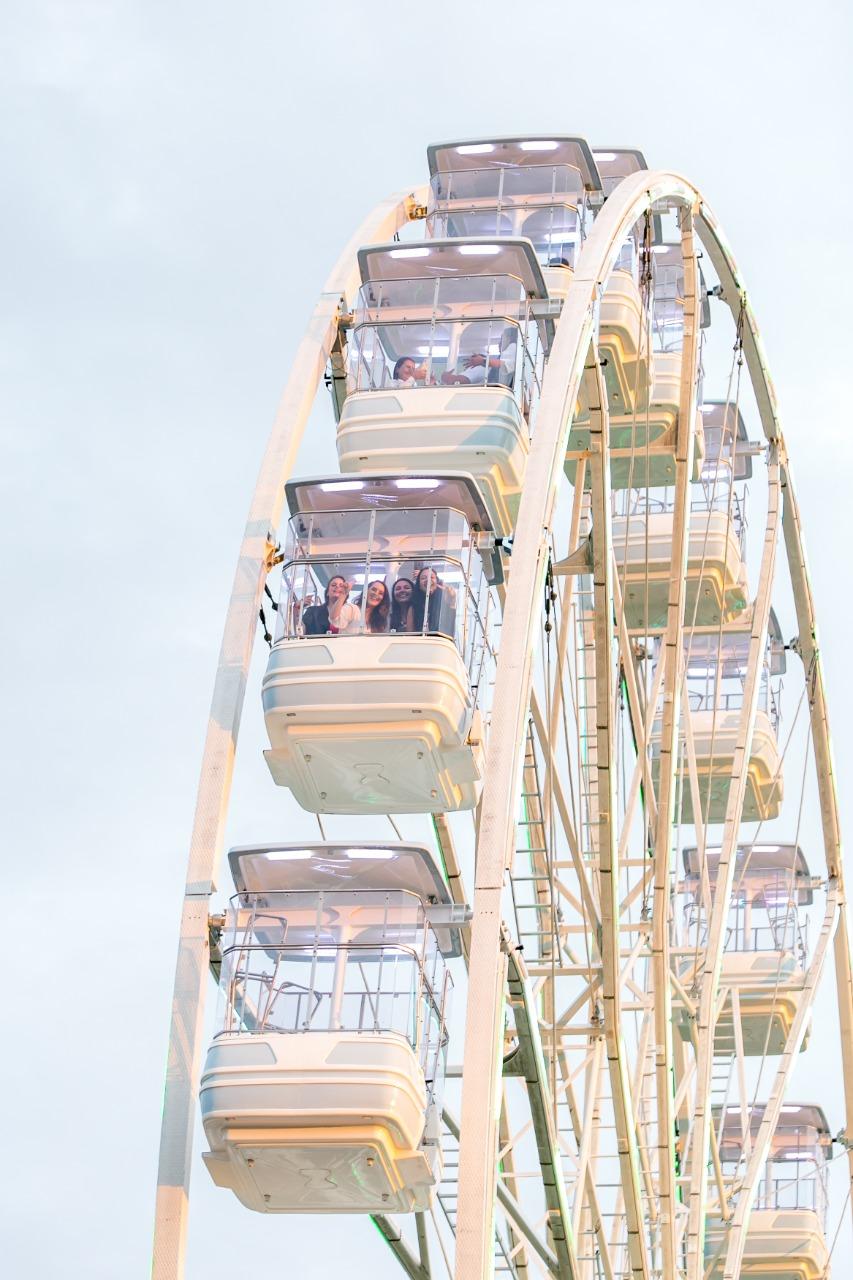Foto capta parte de uma roda-gigante branca girando. De longe, em uma das cabines, é possível ver mulheres sorrindo para a foto
