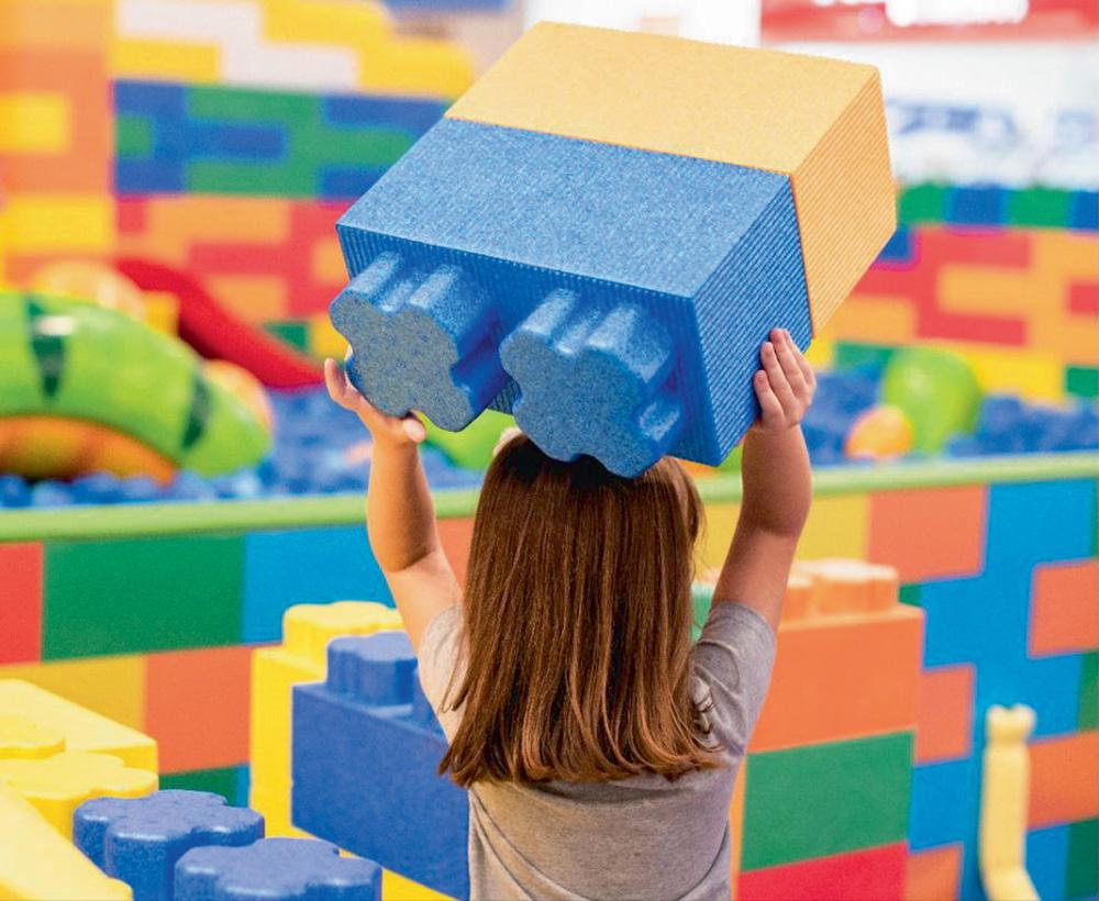 Menina segura um bloco de montar gigante. Em volta dela há vários iguais e coloridos