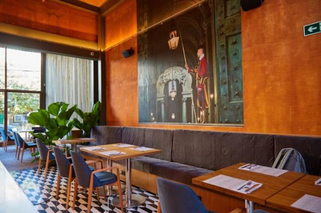Salão do restaurante Moma Modern Mamma Osteria em Pinheiros. Com chão quadriculado preto e branco, paredes alaranjadas e mesas à direita.