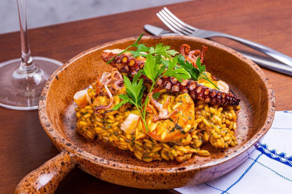 Panelinha alaranjada de pedra com arroz amarelado coberto por camarão, tentáculo de polvo e ramo de salsinha sobre mesa de madeira.