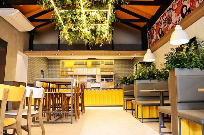 Salão da lanchonete Eggy com cabines com mesas à direta e mesas à esquerda. Ao fundo o balcão de pedidos.