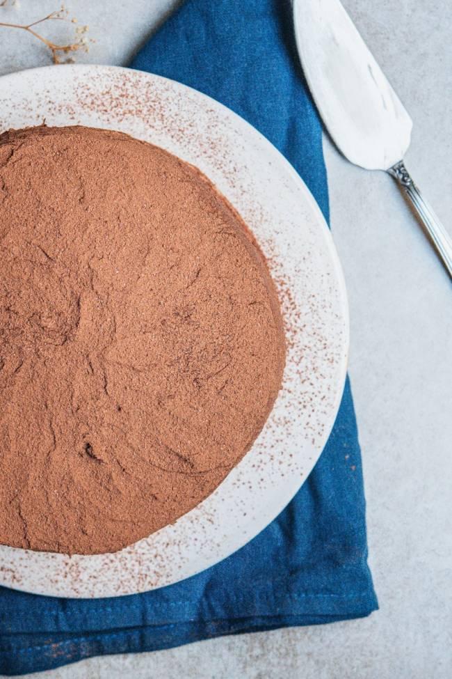 Foto aérea de bolo de chocolate em prata de louça branca sobre toalha azul.
