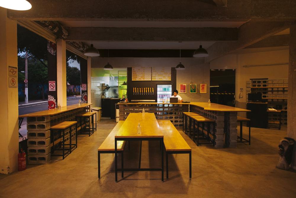 Salão da Cervejaria Central na Barra Funda, em meia luz com mesas e bancos longos de madeira ao centro, direita e esquerda.