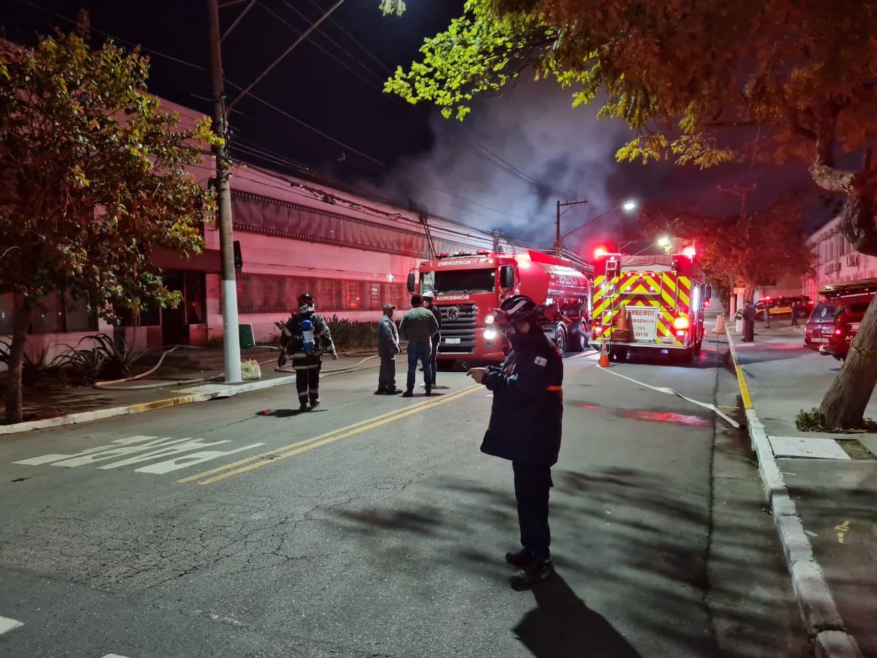 Imagem mostra rua com carros do corpo de bombeiros e edifício, de onde sai fumaça