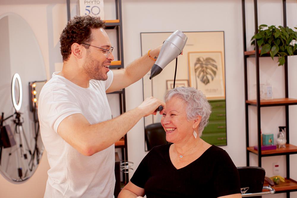 abner e telma estão sorrindo enquanto ele cuida do cabelo dela, com um secador em uma mão e uma escova em outra
