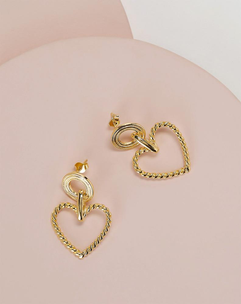 Par de brincos dourados em formato de coração em um fundo rosa