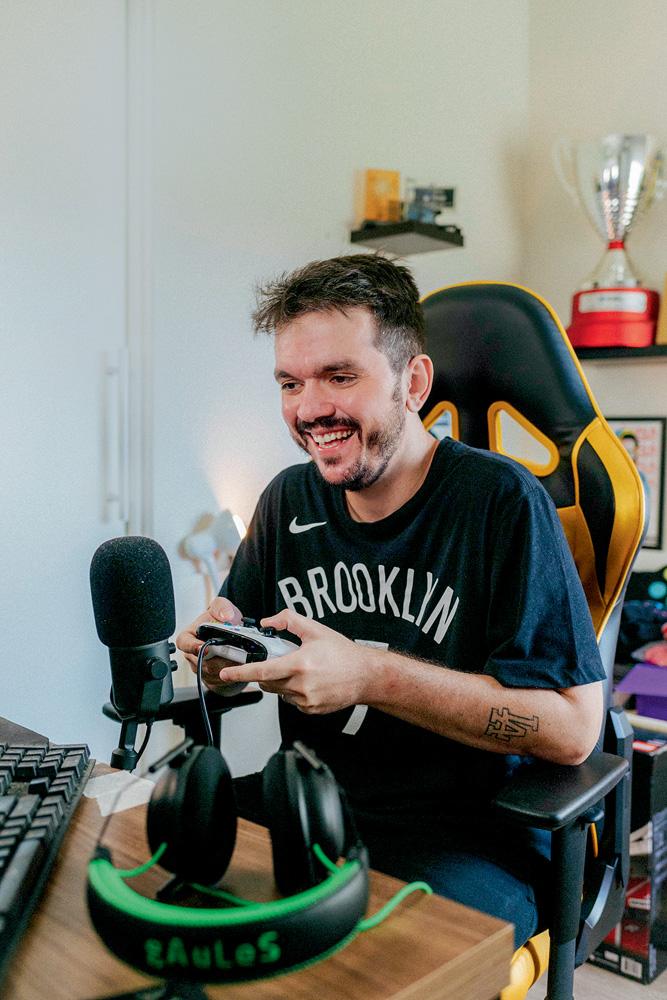 A imagem mostra Gaules, sentado em uma cadeira gamer, rindo para seu monitor e segurando um controle de videogame. Há um microfone profissional na sua frente também.