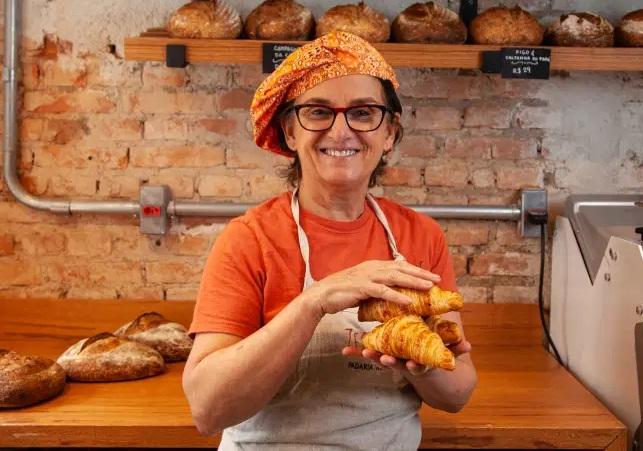 Mulher com avental e pães na mão possa em frente a prateleiras de pães