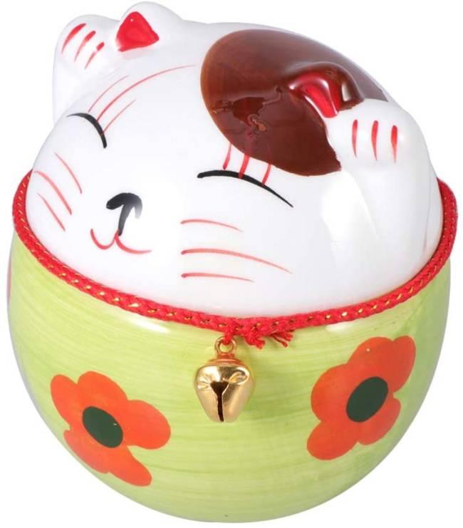 Um cofrinho de moedas de forma arredondada estampado com um gatinho da sorte japonês