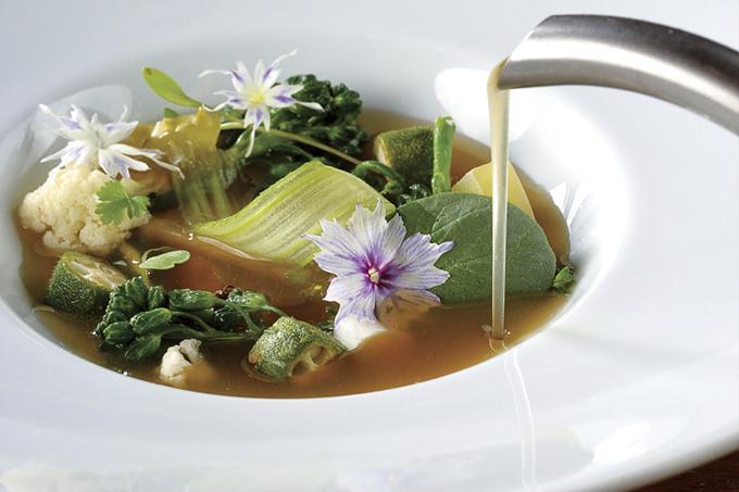 Consomê sendo servido por bule à direita em prato fundo de louça branca com hortaliças.