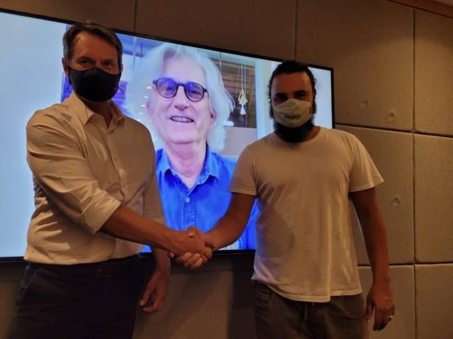 Dois homens de máscara dando um aperto de mãos em frente a um telão.