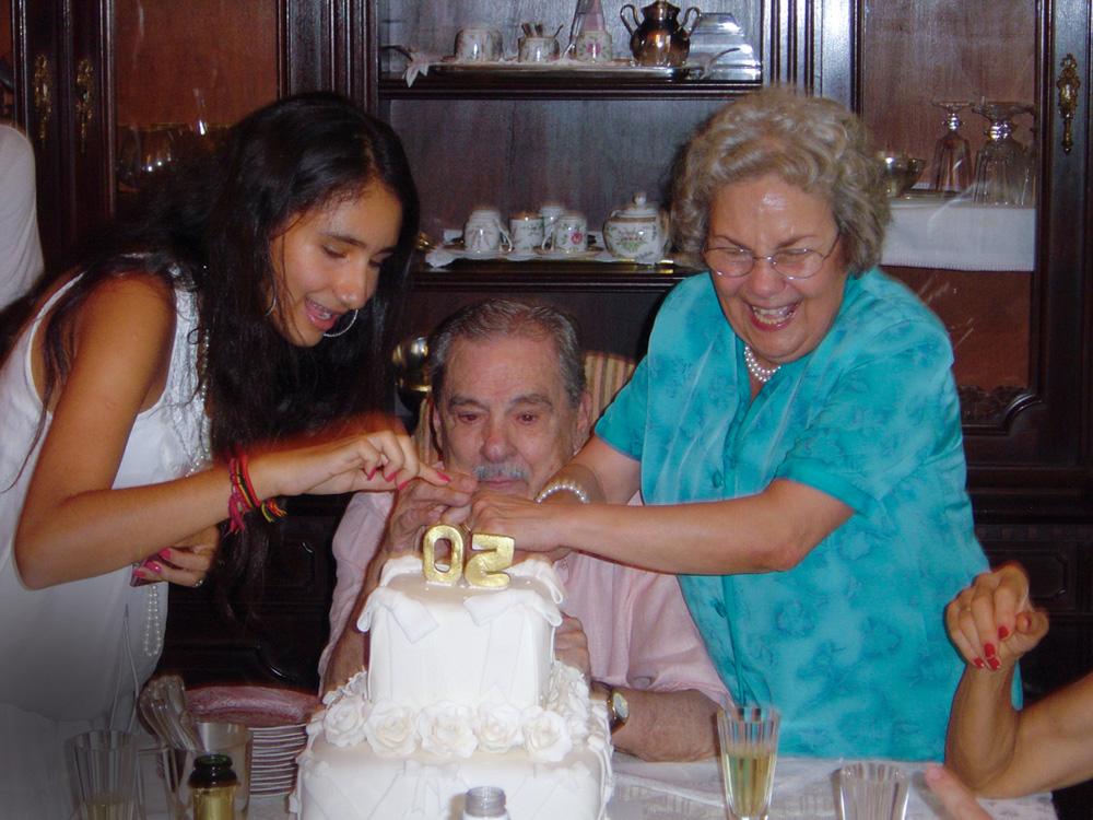 gabriela junto de seus avós, lúcio e elvira, com o bolo dos avós na frente. eles estão cortando o bolo, com as mãos juntas na faca. gabriela e elvira estão de pé e sorriem, enquanto lúcio está com expressão fechada