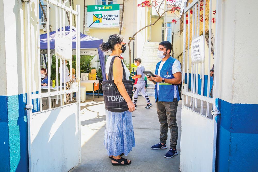 Igor da Silva nos portões de uma unidade básica de saúde segurando tablet e conversando com mulher