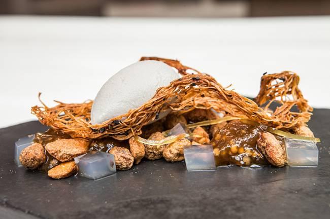 Sobremesa da lama ao caos da chef Helena Rizzo sobre prato escuro.